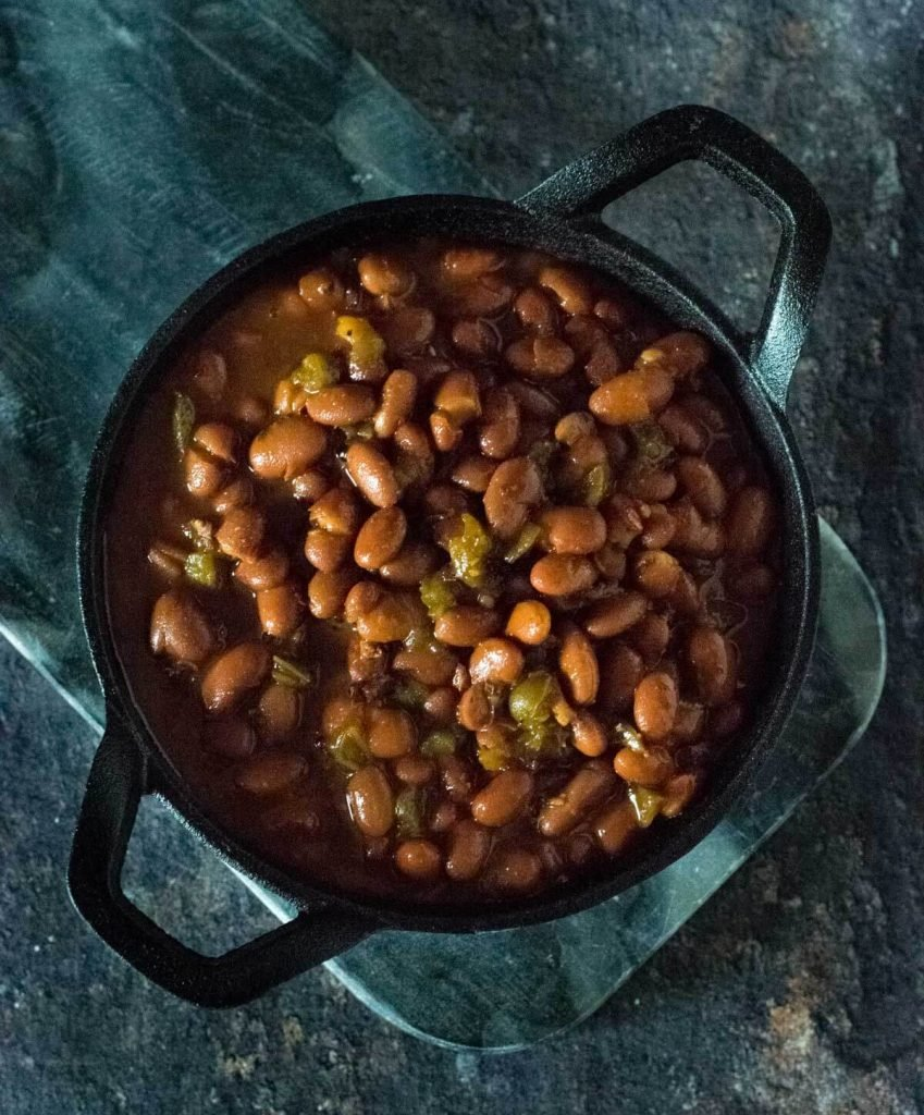 Smoked baked beans in cast iron pan.