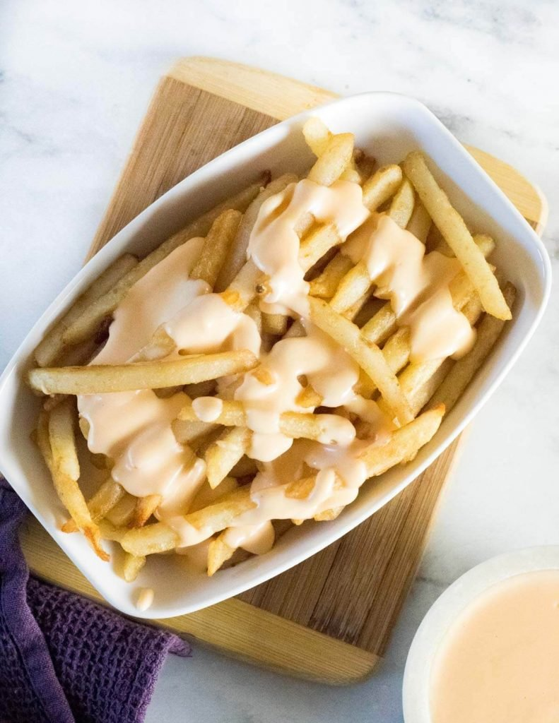 Cheese fries on wooden board.