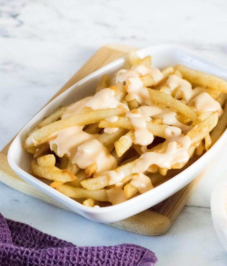 Cheese sauce for fries in white dish.