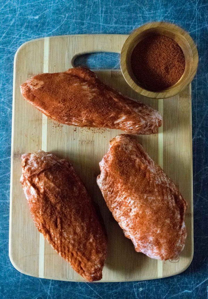 Raw turkey wings dusted with seasoning.
