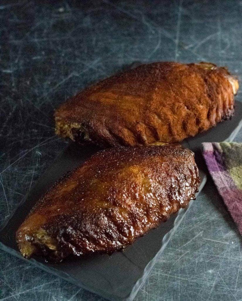 Smoked turkey wings on dark board.