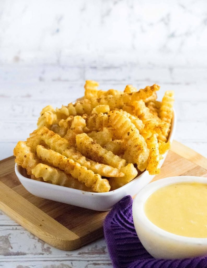 Crinkle cut fries with old bay seasoning and cheese sauce.