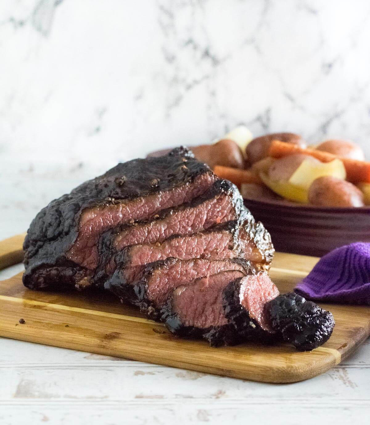 Tender smoked corned beef sliced on cutting board.