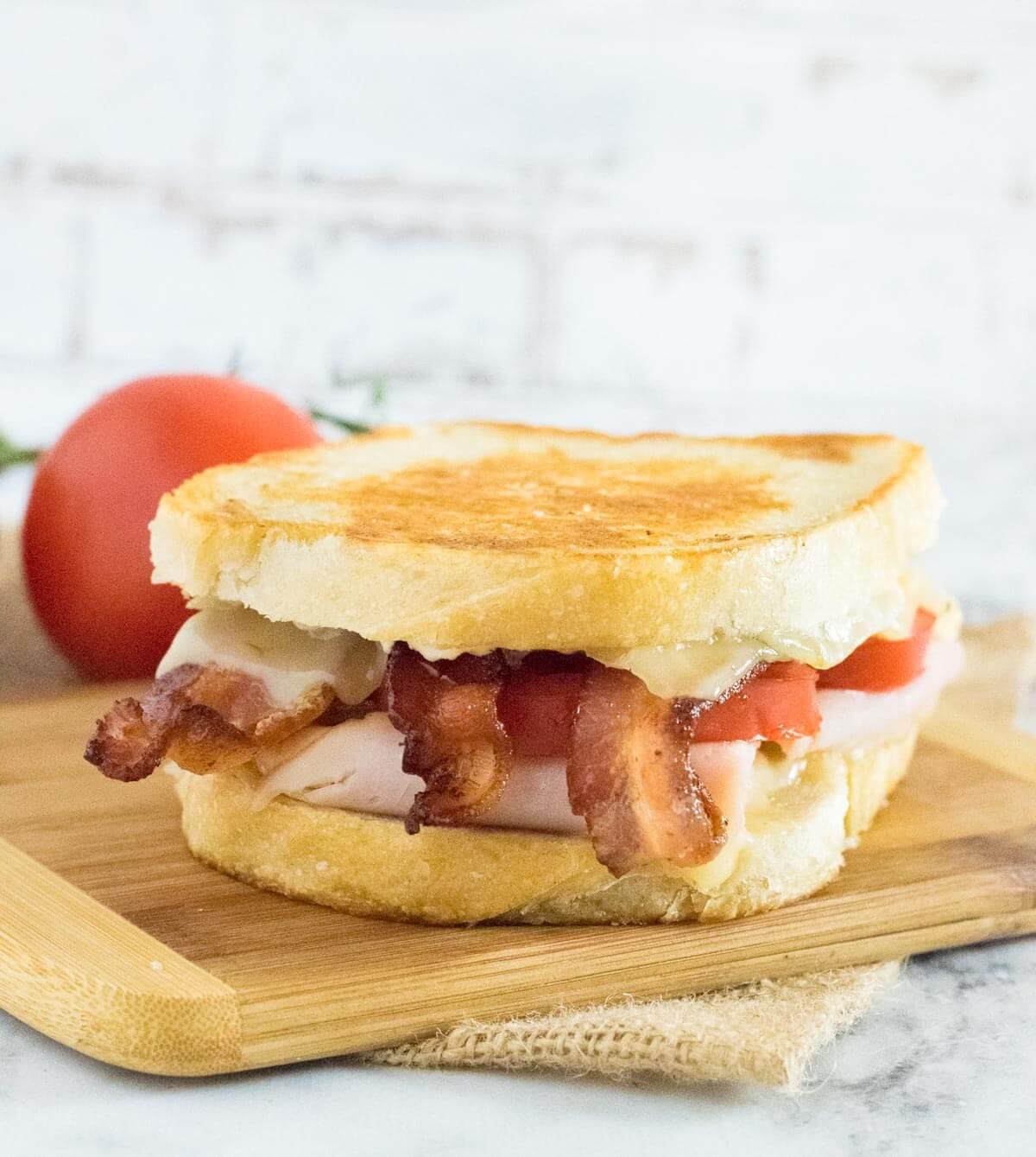 Turkey melt sandwich on cutting board.
