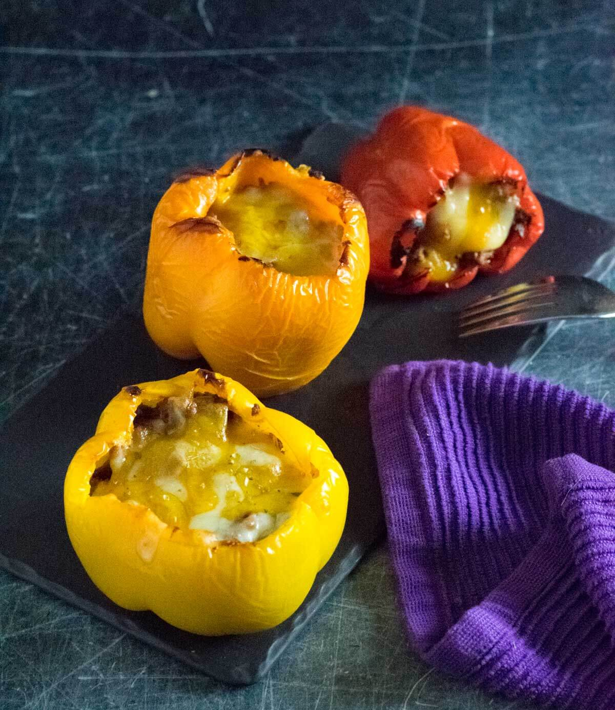 Stuffed bell peppers with beef on black tray.