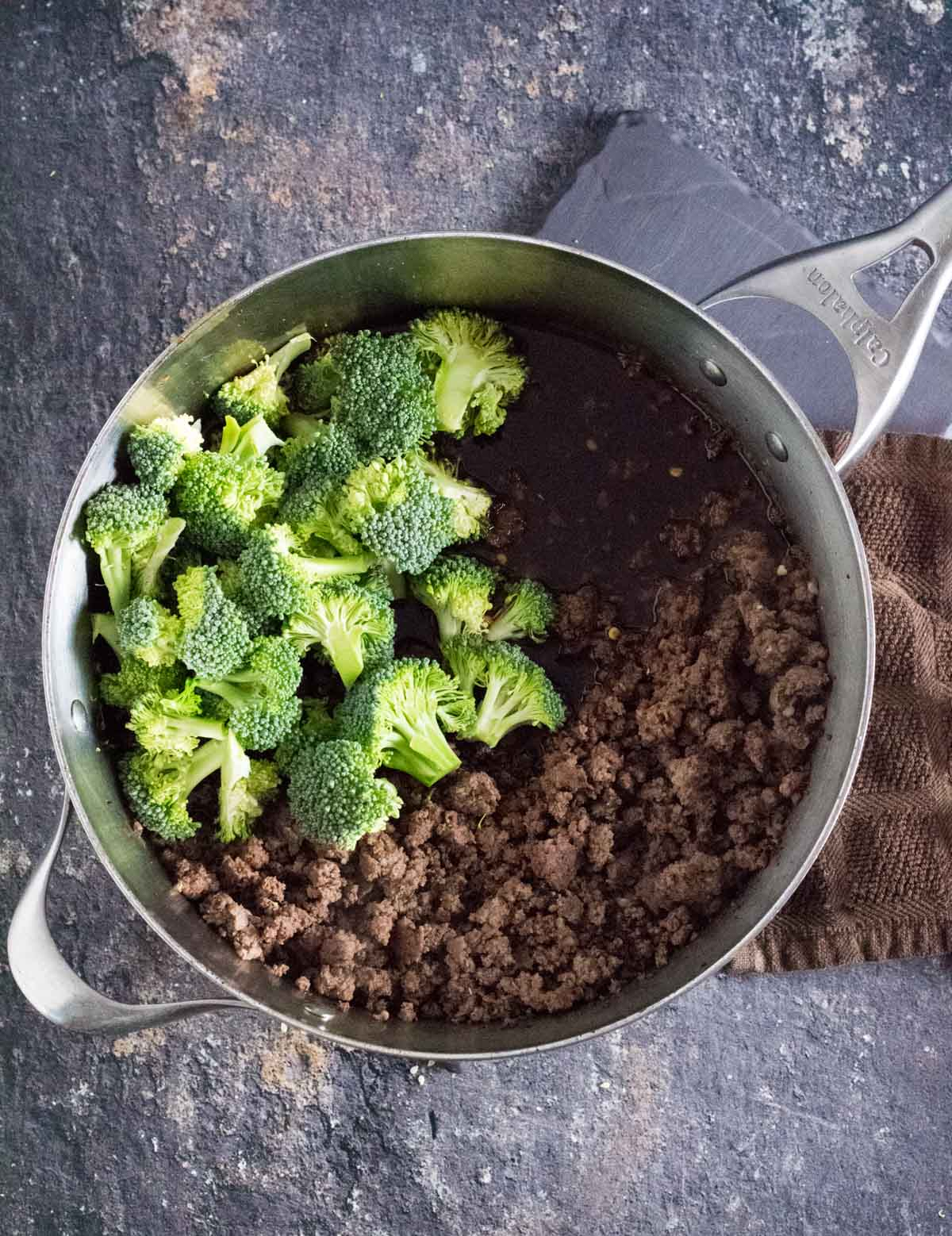 Broccoli florets in skillet with ground beef and stir fry sauce.