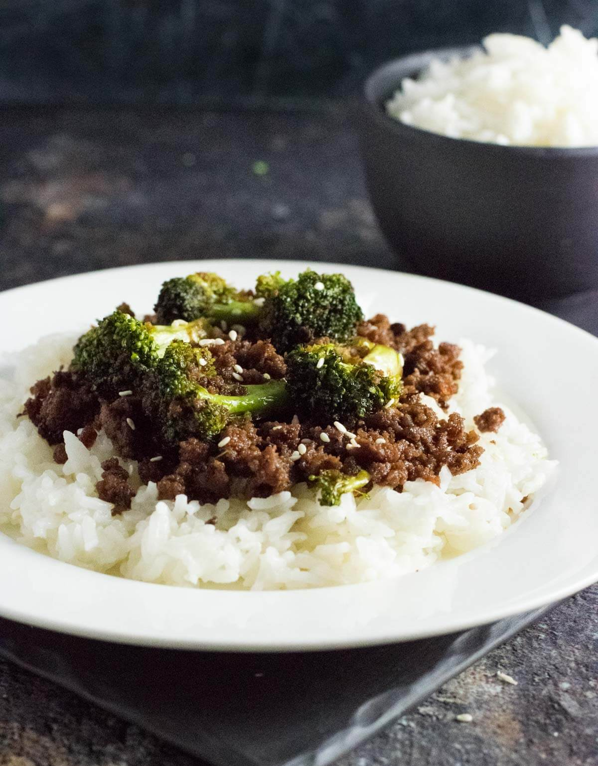 Ground beef and broccoli on a white plate.