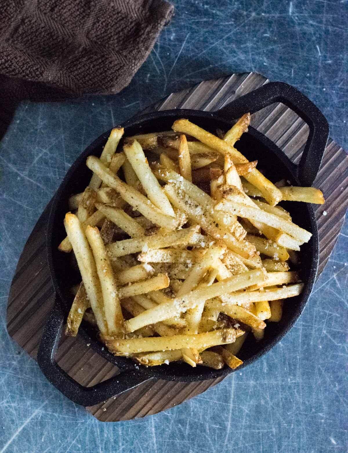 Parmesan truffle fries in black serving bowl.