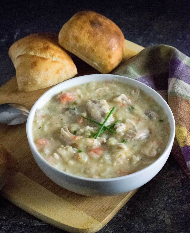 Homemade chicken potato soup in white bowl.